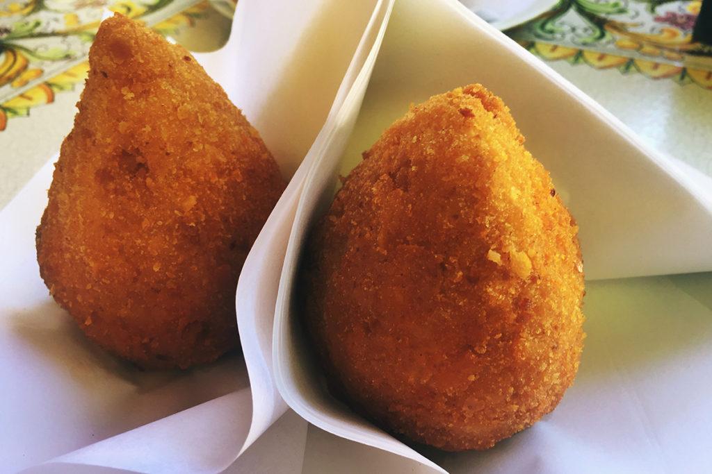 Un plato delicioso, una especie de croqueta rellena de queso o carne con arroz