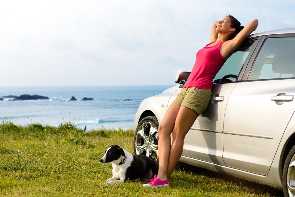 Una mujer apoyada en un coche descansa junto a su perro (iStock)